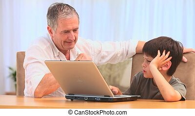 A boy and his grandfather using a laptop in the living room