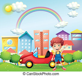 A boy and his red car near the high buildings