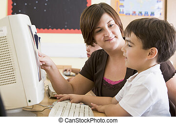 A boy and his teacher working on a computer at primary school