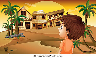 A boy at the desert standing in front of the wooden houses