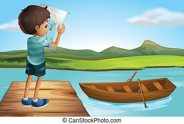 A boy at the river with a wooden boat