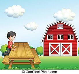 A boy at the table near the barnhouse