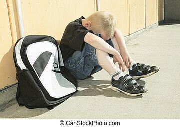 A boy bullying in school playground