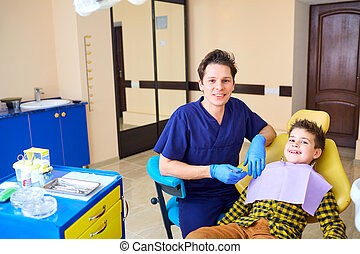 A boy child and a dentist man  in the dentist's office