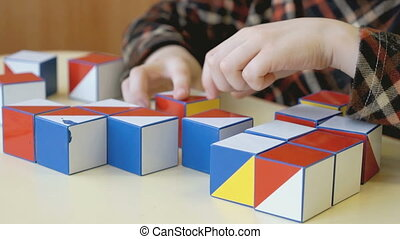 A boy collecting a pattern using colored cubes
