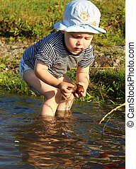 A boy collects reeds on the shore of a lake