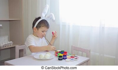 A boy dressed as a hare paints an Easter egg