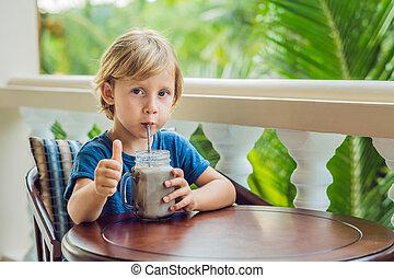 A boy drinks a drink from a carob.