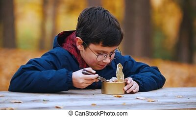 A boy eating canned stewed meat using a knife. Camping