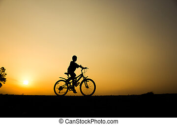 A boy fitness silhouette sunrise cycling workout wellness concept.