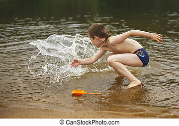 A boy have fun playing with a spray of water in the river at summer. copy space