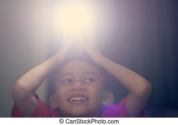 A boy holding a camera flash on his head