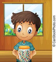 A boy holding a jar of candy balls