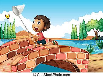 A boy holding a net catching a butterfly