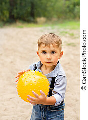 boy holding a yellow ball in her hands