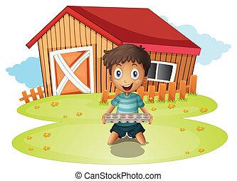 A boy holding an egg tray