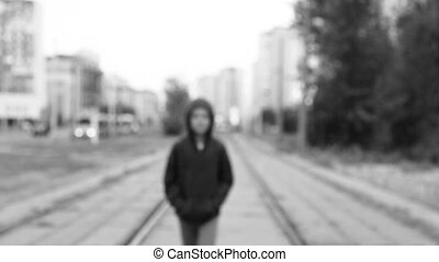 A boy in a black hood on the street - The child in a black...