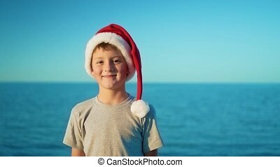A boy in a Christmas hat is standing against the sea and smiling