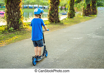 A boy in a helmet riding a scooter in the park