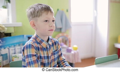 A boy in a plaid shirt sits on a chair in front of the camera with a microphone on his clothes and answers questions.
