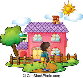 A boy in front of the big pink house