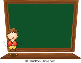 A boy in front of the empty blackboard