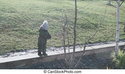 A boy in overalls and a winter hat plays with tree branches on the shore of a pond in a city park