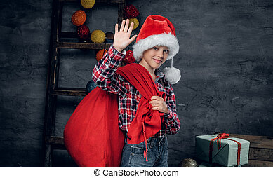 A boy in Santa's hat holds New Year gift sack.