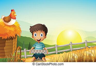 A boy in the farm holding an empty egg tray