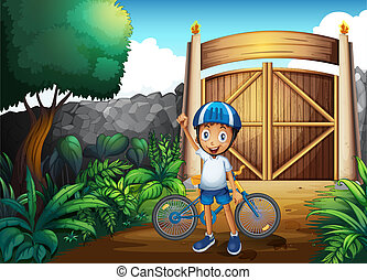A boy in the frontyard with a bike