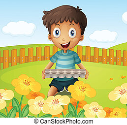A boy in the garden holding an empty egg tray