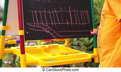 A boy in the open air draws with chalk on the Board. Close up of his hand