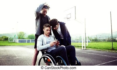 A boy in wheelchair and his teenager friends using a...