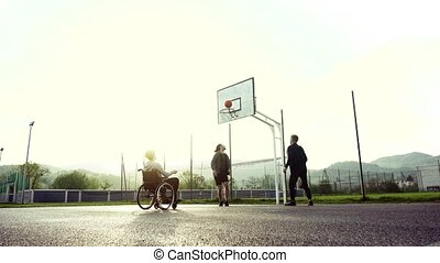 A boy in wheelchair with teenager friends outside playing basketball.