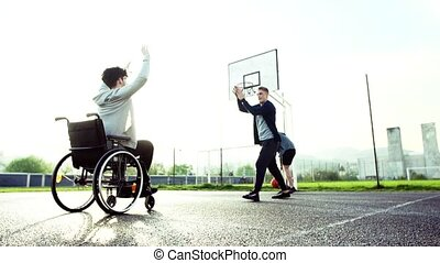 A boy in wheelchair with teenager friends outside playing...