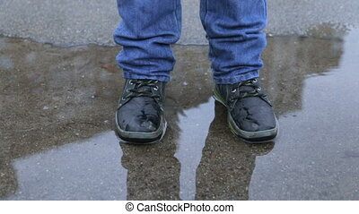 A boy in winter boots jumping in a puddle - A child in...