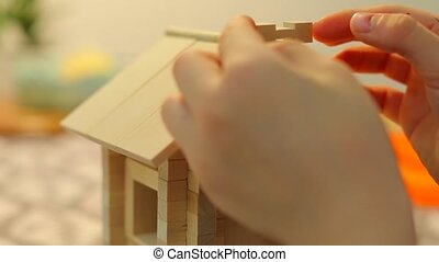 A boy is building a toy house. He puts the details the roof and seeks balance.