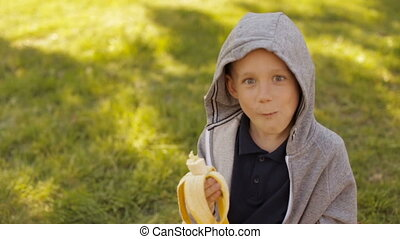 A boy is eating a fresh banana in a summer park - A child is...