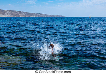 A boy is jumping from the cliff into the sea wiht big water splash on a hot summer day. Holidays on the beach. The concept of active tourism and recreation