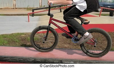 A boy is riding BMX cycling tricks in a skateboard park on a sunny day. Super Slow Motion