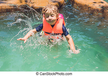 A boy jumps into the water in a pool