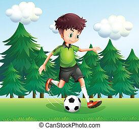 A boy kicking a soccer ball near the pine trees -...