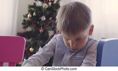 A boy near christmas tree doing something