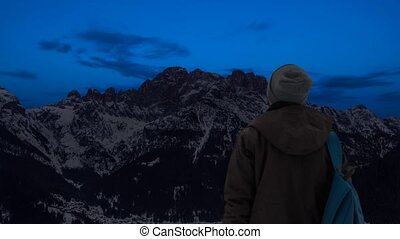 A boy observes the passage from day to night and the moon rises in the mountains
