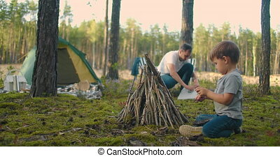 A boy of 3-4 years helps to put sticks in a campfire during a trip to the forest as a family in nature. Family holiday in the woods with tents