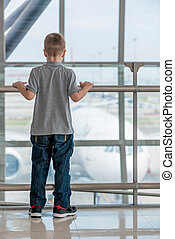 A boy of 7 years standing at the airport watching the plane