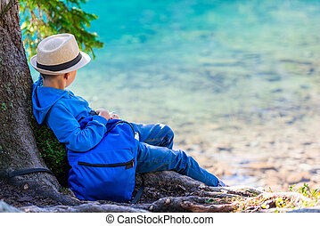 A boy of 8 years with a backpack resting by the lake in the Tatras