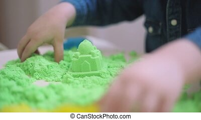 A boy of green kinetic sand molds shapes and figures,HD...