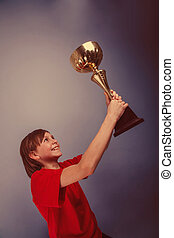 a boy of twelve European appearance holds the cup, the reward, t