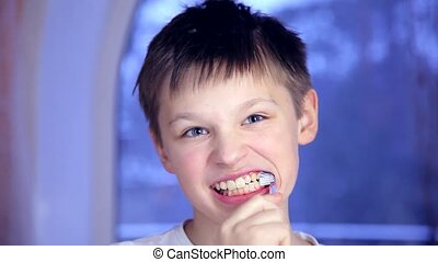 A boy on a blue background brushing his teeth and then chattering teeth